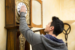 Young man checking a pendulum and winding the Royalty Free Stock Photos