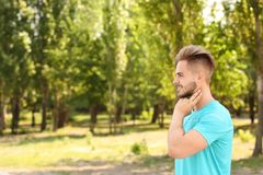 Young man checking pulse outdoors len. Young man checking pulse outdoors on sunny day stock photography