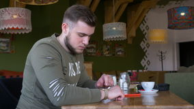 Young man checking smart watch and phone devices while sitting at a table. Young man checking smart watch and phone devices while sitting at restaurant table stock footage