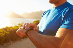 Young man checking time on his sports watch Stock Image