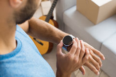 Young man checking time on watch planning relocation Royalty Free Stock Image