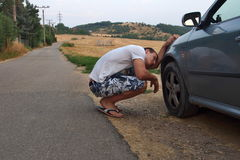 Young Man Checking a Wheel on His Car. Young guy checking a wheel on his car somewhere in countryside Stock Photos
