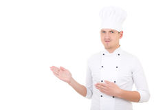 Young man chef showing or presenting something isolated over white. Young man chef showing or presenting something isolated on white background stock photo