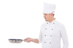 Young man in chef uniform holding frying pan isolated on white Royalty Free Stock Photo