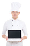 Young man in chef uniform holding laptop with blank screen isola Royalty Free Stock Photography
