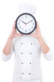 Young man chef in uniform holding office clock behind his face i Stock Image