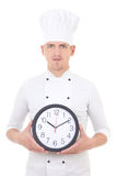 Young man chef in uniform holding office clock isolated on white Royalty Free Stock Photo