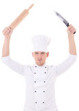 Young man in chef uniform holding roller pin and knife isolated Royalty Free Stock Photography