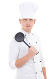 Young man in chef uniform with sauce spoon isolated on white Stock Photos