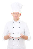 Young man chef  in uniform showing empty plate isolated on white Stock Images