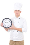 Young man chef in uniform showing office clock isolated on white Stock Images
