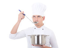 Young man in chef uniform tasting something from saucepan isolat Royalty Free Stock Images