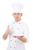 Young man chef  in uniform thumbs up and showing empty plate iso Stock Image