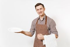 Young man chef or waiter in striped brown apron, shirt holding white round empty clear plate, towel napkin isolated on royalty free stock photo