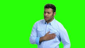Young man with chest pain on green screen. Indian guy suffering from heart ache on Chroma Key background. Health problem concept stock video