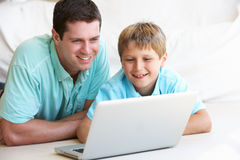 Young man with child on laptop computer Royalty Free Stock Photos