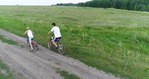 A young man with a child riding bicycles on a country road. Shooting from a drone. Sports outdoors. A young man with a child riding bicycles on a country road stock video