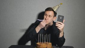 Young man with chocolate cake and a candles playing with party blowers and takes selfie royalty free stock photos
