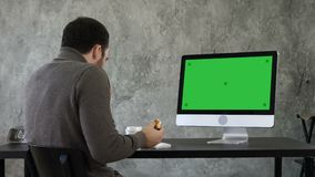 Young man choking while eating and watching something on the computer in the office. Green Screen Mock-up Display. Back view. Young man choking while eating and stock video footage