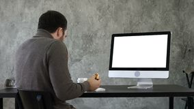 Young man choking while eating and watching something on the computer in the office. White Display. Back view. Young man choking while eating and watching stock video footage