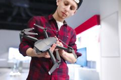 Young man chooses Quadcopter in a drones store. Buy a drone in a technology store. A young man chooses Quadcopter in a drones store. Buy a drone in a technology royalty free stock photography