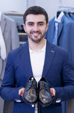 Young  man chooses a shoes  at a shop. Stock Photography