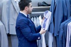 Young  man chooses tee - shirt at a shop. Stock Photos
