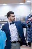 Young  man chooses tee - shirt at a shop. Royalty Free Stock Photos
