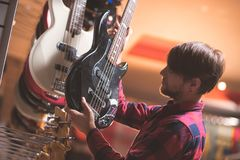 Young man choosing a bass guitar. In a music store stock photography