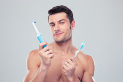 Young man choosing brush over gray background Stock Image