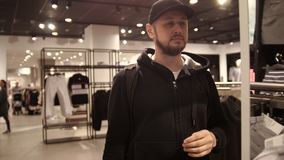 Young man is choosing cap in mall or clothing store - shopping, fashion, style stock video