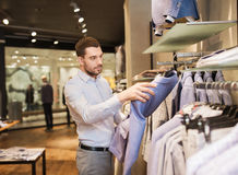 Young man choosing clothes in clothing store. Sale, shopping, fashion, style and people concept - elegant young man in shirt choosing clothes in mall or clothing Royalty Free Stock Image