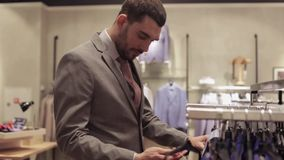 Young man choosing clothes in clothing store stock video footage