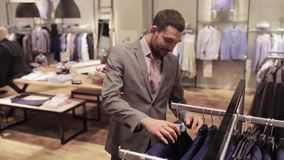 Young man choosing clothes in clothing store stock video