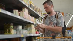 Young man is choosing goods in grocery in supermarket, frontal view stock video