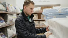 Young man is choosing a mattress in a big furniture shop or supermarket. He is checking its elasticity, memory foam by