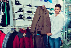 Young man choosing new coat in sports store Royalty Free Stock Photography