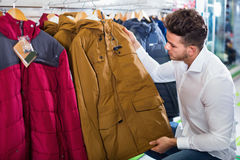 Young man choosing new coat in sports store Stock Image