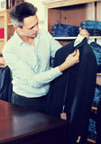 Young man choosing new suit in male store Stock Photography