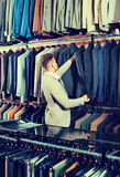 Young man choosing new suit in men's cloths store. Young  cheerful  man choosing new suit in men's cloths store Stock Photos