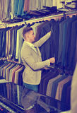 Young man choosing new suit in men's cloths store Royalty Free Stock Photos