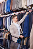 Young man choosing new suit in men's cloths store. Young pleasant cheerful positive man choosing new suit in men's cloths store Royalty Free Stock Photography