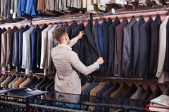 Young man choosing new suit in men's cloths store. Young pleasant positive man choosing new suit in men's cloths store Stock Photo