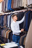 Young man choosing new suit in men's cloths store. Young  positive man choosing new suit in men's cloths store Stock Photos