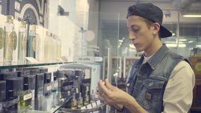 Young man choosing perfume in a beauty store stock footage