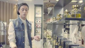 Young man choosing perfume in a beauty store stock video footage