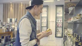Young man choosing perfume in a beauty store stock video