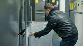 Young man is choosing a refrigerator in a store. He is opening the doors, looking inside