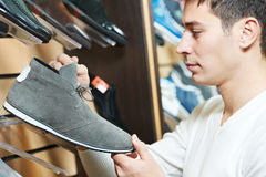 Young man choosing shoe in clothes. Young man choosing shoes during footwear shopping at shoe shop Royalty Free Stock Image