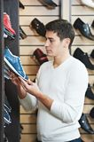 Young man at choosing shoe in clothes store Royalty Free Stock Images